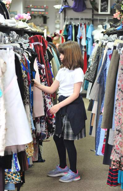 Nine year old Ellie Spalding helps her grandmother look for the right attire Wednesday at the recently re-opened Bread and Roses Thrift & More store.