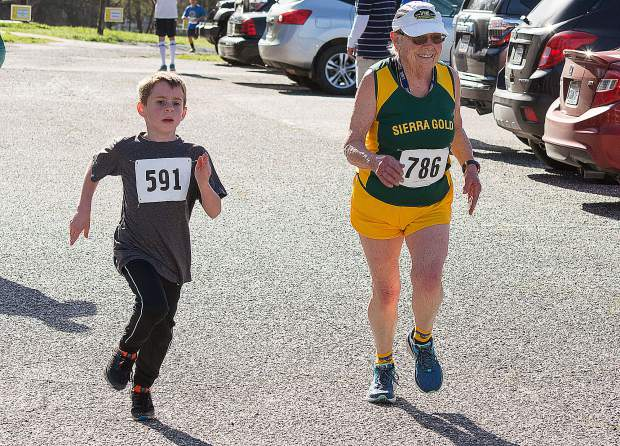Photo by John Hart The Joanie Bumpus 18th annual 5K, 10K, and walk, Daffodil Run, Sunday morning, Western Gateway Park, Penn Valley. Eric Romeo 7 years, Penn Valley(l) and Lynne Hurrell, 83 years from Grass Valley running to the finish line of the run.