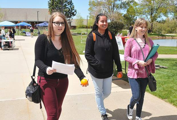 Sierra College's Taylor Gemignani (from left) Jessica Urzua, and Eryn Westervelt, walk in between the Earth Day booths set up in the campus' quad Wednesday. The trio used the day to get extra credit for history and geology.