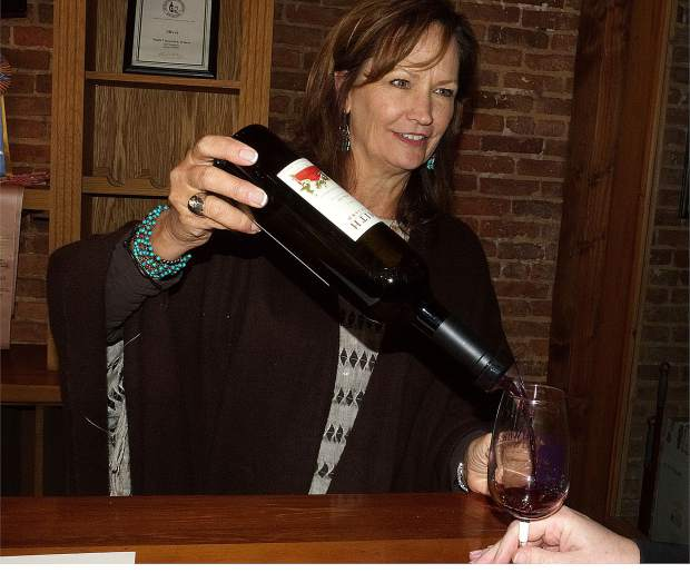 Chris Smith, owner of Smith Vineyard, pours wine into a glass at Smith Vineyards Tasting Room on Mill Street during Saturday's Foothills Celebration. Smith and her husband, Gary, have announced their plans to retire. The tasting room will be open through May.