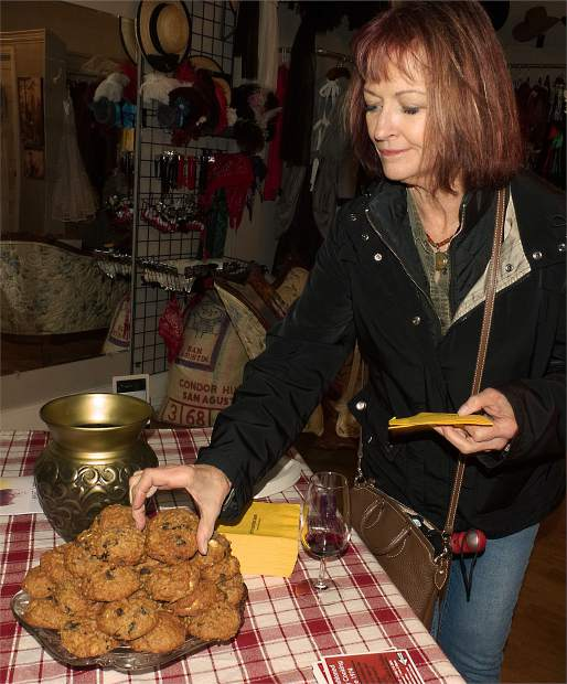Sheri Moura of Auburn reaches for homemake cookies by Bierwagen's Happy Apple Kitchen at Three Lillies Photography on Mill Street in downtown Grass Valley Saturday.