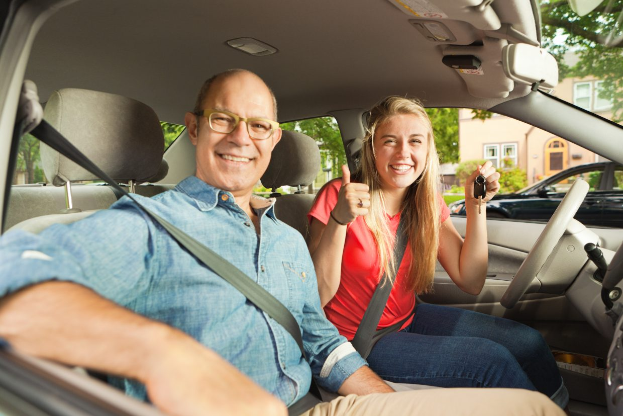 A happy teenager young woman receiving a new car from her parent father. The young woman is holding the key to the car and they are smiling and posing for the camera inside their new car.