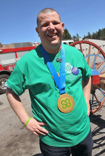 Sean Painter smiles as he wears a gold St. Baldricks medal, awarded to him for being the highest single fundraiser, bringing in $2,200 to have his head shaved.
