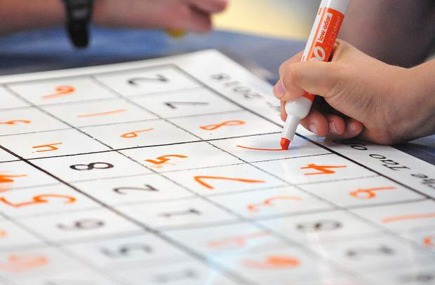 A sudoku tournament participant places the final number into the grid before raising their hands to have the judges check their accuracy.