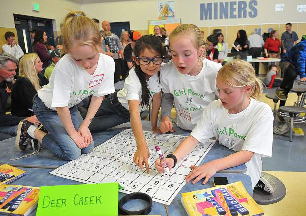Deer Creek 3rd graders McKinlee Smith (from left), Sarah McBride, Whitney Parnow, and Elle Piland work diligently on their sudoku card while spectators look on. The group was recognized for having the best outfits with their shirts that read 'Girl Power Deer Creek Sudoku' on them.