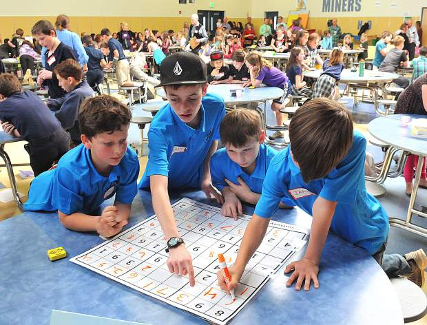Echo Ridge Elementary School students' Jude Richards (from left), Ethan Echternacht, Jayden Echternacht, and Jaron Richards, work as swiftly as they can on a double-sided Sudoku grid during Thursday's Sudoku tournament held at Nevada Union High School. The Echo Ridge students' efforts would be accurate and quick enough to earn them third place among 27 different teams from nine different schools and nearly 100 other children between second and sixth grades.