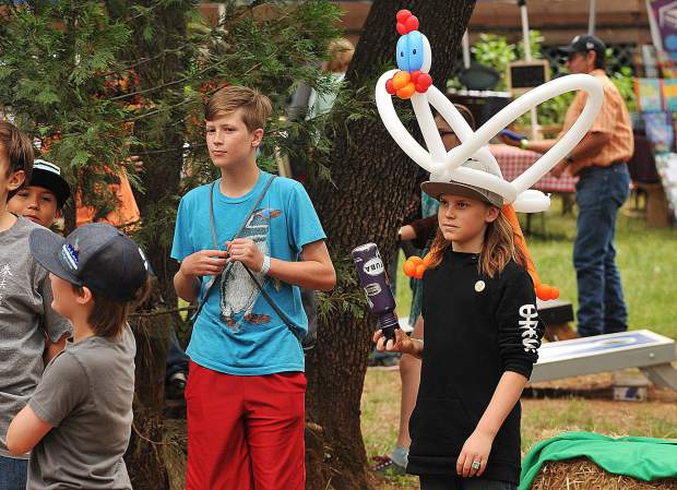 Blue Marble Jubilee youth attendees watch the entertainment on the main stage while donning their favorite balloon hats and creations.