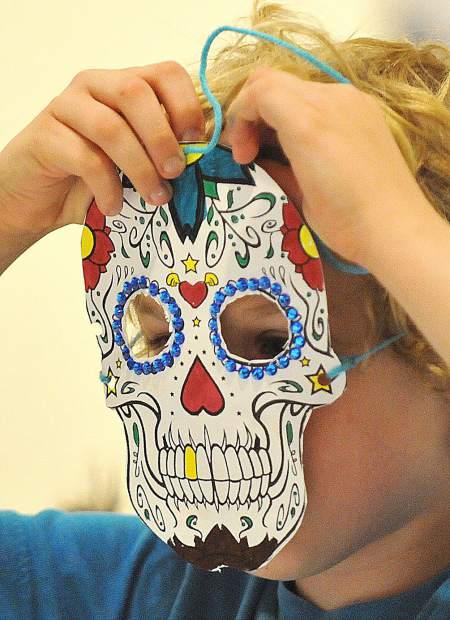 Ten year old Rylan Gregory Johnson test fits a Dia De Los Muertos sugar skull mask that he has made during the family fun day event at the Center for the Arts.