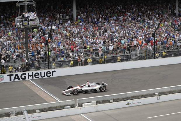 Will Power, of Australia, takes the checkered flag to win the Indianapolis 500 auto race at Indianapolis Motor Speedway in Indianapolis, Sunday.
