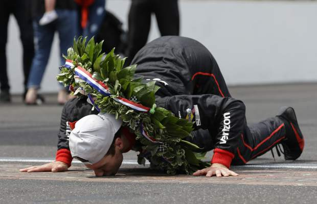 Will Power, of Australia, kisses the yard of bricks on the start/finish line as he celebrates winning the Indianapolis 500 auto race at Indianapolis Motor Speedway, in Indianapolis Sunday.