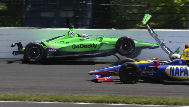 Alexander Rossi drives by Danica Patrick as she hits the wall in the second turn during the running of the Indianapolis 500 auto race at Indianapolis Motor Speedway, in Indianapolis Sunday.