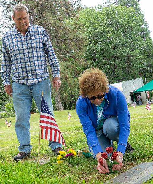 Jack and Marie Personeni Stillens tend to the grave of Lynn Williams, a U.S. Army veteran who served during World War I, at New Elm Ridge Cemetery on Kidder Street in Grass Valley. Marie Personeni Stillens also placed hearts at the resting place of her family member, Donald Personeni, Saturday morning.