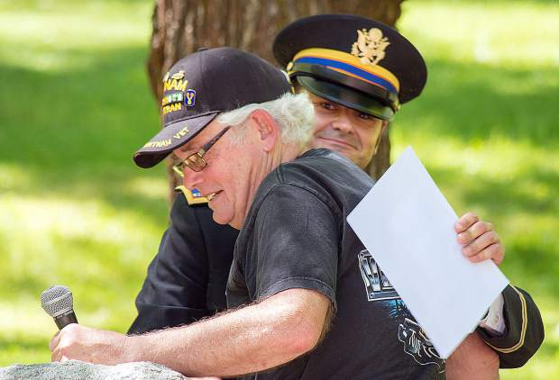 Will Buck, CW2, U.S. Army (retired), right, and emcee of the program at Memorial Park gives Tom Munroe, U.S. Army SPC4, a Vietnam Veteran, a hug after his speech.
