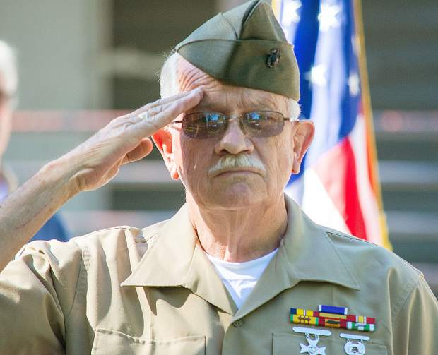 Herbert Gardner Jr., of the U.S. Marine Corps, salutes during the playing of Taps at Pioneer Park.