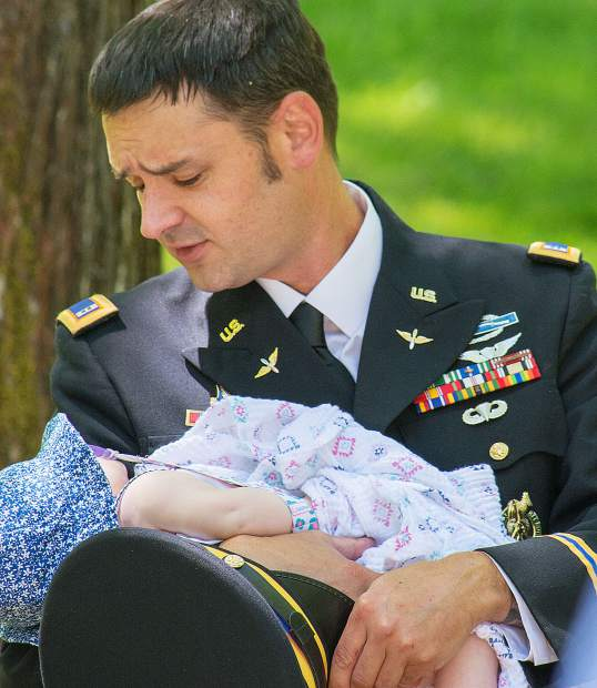 "Will Buck, CW2, US Army (Ret.), holds his daughter Scarlett Buck, 5 months, during the singing of ""God Bless The USA,"" by Barbra ""Babs"" Conner."