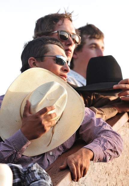 Cowboys competing in the Penn Valley rodeo place their hats over their hearts as the star spangled banner is sung prior to Friday night's opening festivities.