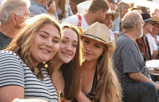 Penn Valley friends Izabella Votino (from left) Hannah Young, and Katie LaValley, smile as they await the beginning of the Penn Valley Rodeo Friday evening in Penn Valley.