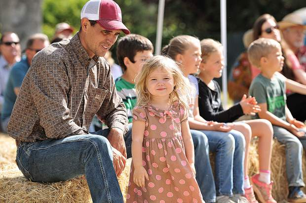 David Bartow and his two-year-old daughter Braelynn enjoy the music from Hale Family and Friends' Cowboy Church band Sunday at the Penn Valley Rodeo Grounds.