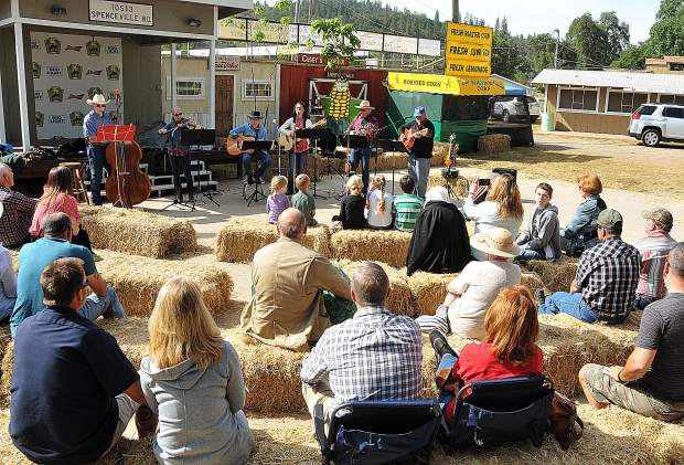 Folks gather around the Hale Family and Friends country Christian six piece band during Sunday morning's Cowboy Church at the Penn Valley Rodeo Grounds.