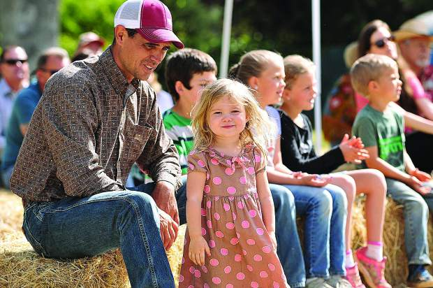 David Bartow and his two year old daughter Braelynn, enjoy the music from Hale Family and Friends' Cowboy Church band Sunday at the Penn Valley Rodeo Grounds.