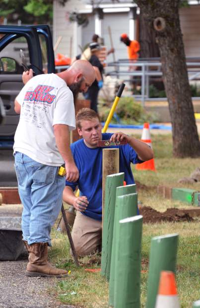 City of Grass Valley Waste Water Collection Department workers John Van Dyk Jr. (left) and George Olson volunteered their time to fix some of the posts that border the parking lot during Saturday's cleanup day.