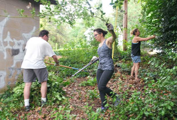 Local insurance agent and writer Grayson Davenport, Citizens for Safe Parks member Aurora Packard, and neighbor Amanda McQuade lend a hand to clear overgrown vegetation from a corner of Memorial Park Saturday morning. Officials have suggested the possiblilty of a childrens mural to help deter from graffiti.