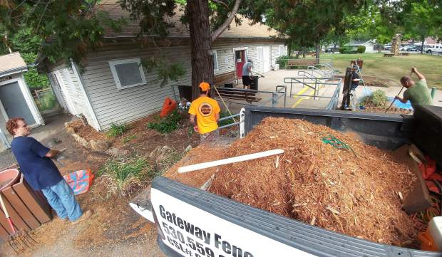 Volunteers help put wood chips into planter boxes at Memorial Park.