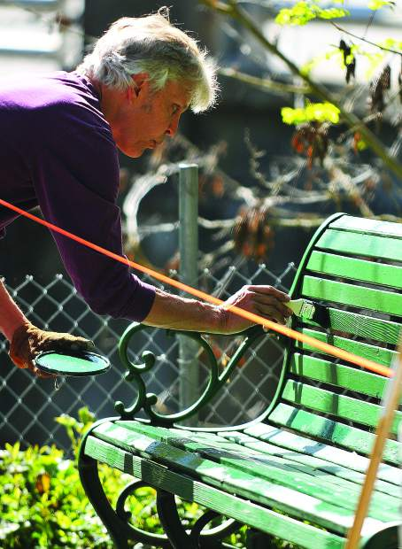 Nevada City resident Jim Morris applies fresh green paint to a bench in the Nevada Street parking lot during Wednesday morning's Nevada City Spring Cleaning event where around 50 volunteers helped spruce up the city.