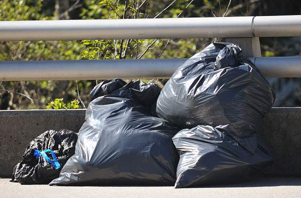 Bags of trash pulled from the Miners Trail under the Highway 49 overpass of Deer Creek, sit along side Broad Street as they await pickup during Tuesday's spring cleaning.