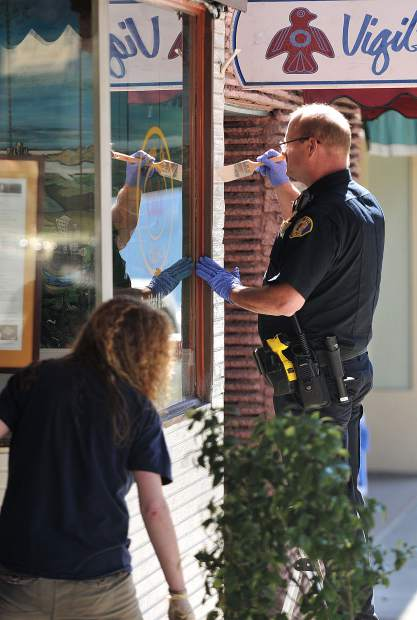 Nevada City Police Officer Paul Rohde, and Nevada City City Manager Catrina Olson, apply paint to a storefront on Broad Street during Tuesday's spring clean event.