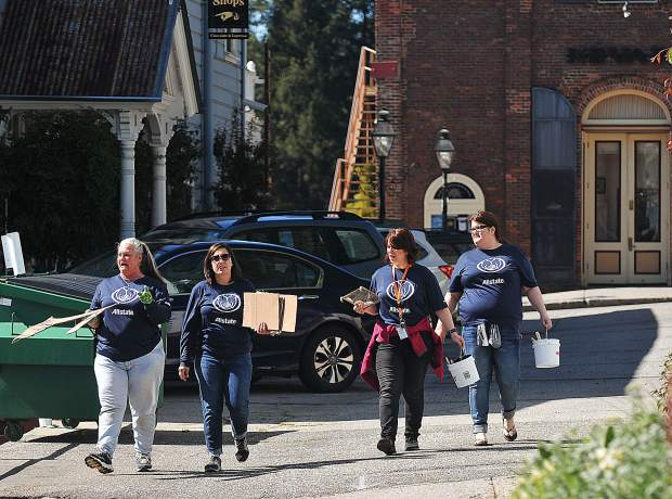 Members of the Allstate Insurance I-Vantage team walk along Commercial Street looking for more downtown gas lamps to paint.