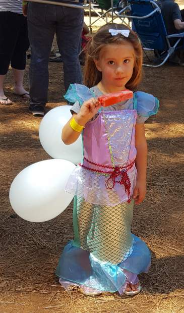 Isabella, dressed as a mermaid complete with balloon tail, gets ready for the children's parade Sunday. Isabella was with parents Fernanda and Joshua Benson, of Petaluma. Joshua Benson attended the festival as a child with his mother, Kathleen Walsh, who also was with them for the festival.