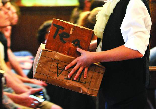 Symbolic boxes of East India Company tea are carried out of Emmanuel Episcopal Church by students following the debate. The meeting was the place where unprecedented numbers of people from all walks of life engaged in debate and dialogue that would change the fate of the nation.