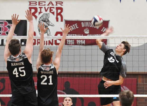 Bear River's Jace Rath hits a spike over a couple Lincoln defenders during Tuesday's victory. Rath led the Bruins with 10 kills.