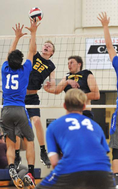 Nevada Union High School senior Tanner Quiggle (22) spikes a ball down forcefully to score a point for the Miners en-route to their win over the Davis Blue Devils in four sets.