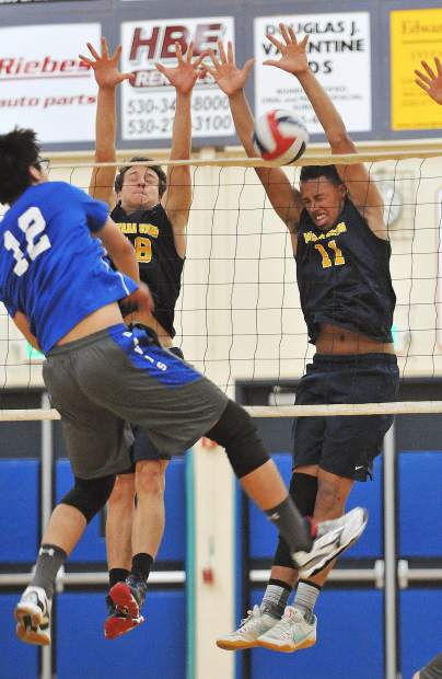 Nevada Union's Preston Nowak (18) and Cameron Dallago (11) make the block for a point against the Davis Blue Devils Tuesday at the Albert Ali Gymnasium in Grass Valley.