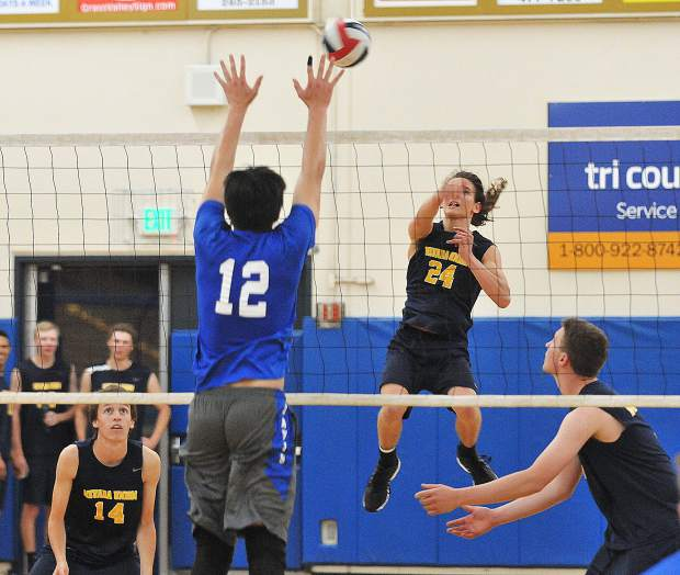 Nevada Union boys volleyball team captain Nick Ashbaugh lobs a ball over during Tuesday night's first round playoff win over the visiting Davis Blue Devils.