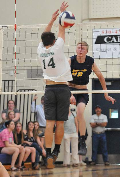 Nevada Union High School 6-foot 5-inch senior Tanner Quiggle watches his spike pass a Ponderosa High School defender during the Miners second round playoff win in three straight sets.