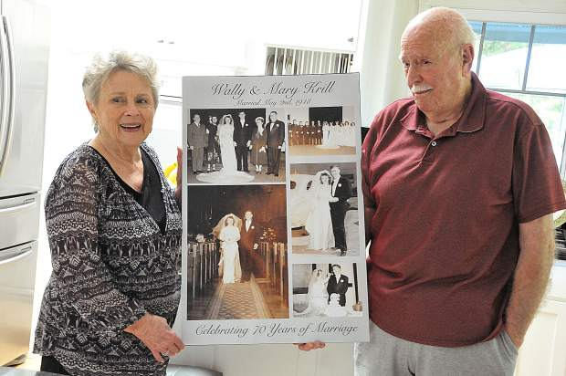 Mary and Wally Krill hold a collage of wedding photos in between them, taken 70 years ago when they were wed.