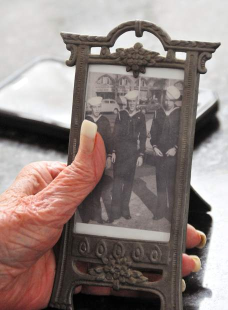 Mary Krill holds a picture of her husband Wally, (center) whom she met while he was serving in the Navy.