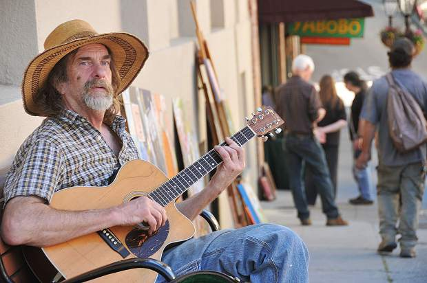 Jim Sontag plays his guitar in a bench along Pine Street during Friday's art walk in downtown Nevada City.