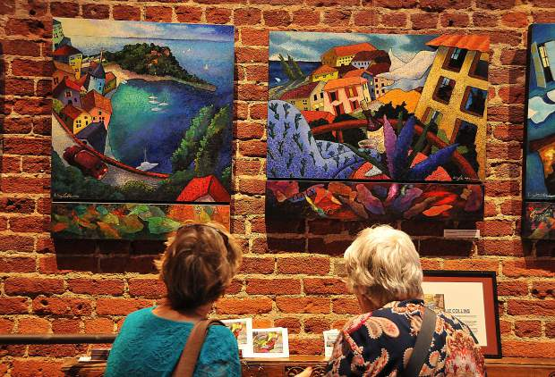 A pair of art walkers admire the work of painter Liz Collins while inside of Szabo Vineyards tasting room.