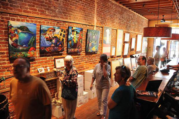 Art walkers peruse the collection of paintings by Liz Collins inside of Szabo Vineyards tasting room off of Broad Street during Friday evening's First Friday Art Walk hosted by the Nevada City Chamber of Commerce.