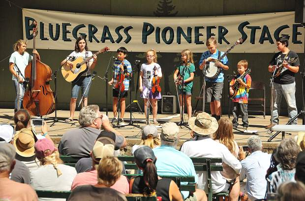 A group of California Bluegrass Association Youth Academy students gather on the Pioneer Stage for their end of camp performances during the Father's Day Bluegrass Festival at the Nevada County Fairgrounds.