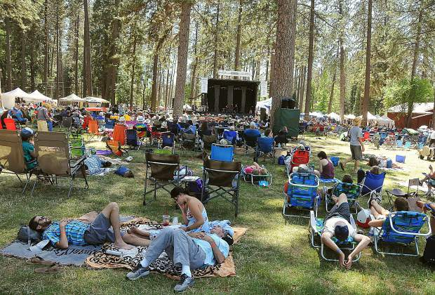 A group of festival goers enjoy some downtime while the bluegrass band Thompsonia plays on the main stage in the background during the 43rd annual Father's Day Bluegrass Festival at the Nevada County Fairgrounds. The festival ended its four-day run this weekend with bands such as The Del McCoury Band, the Edgar Loudermilk Band, the Possum Trot String Band, and the Honeysuckle Possums to name a few.