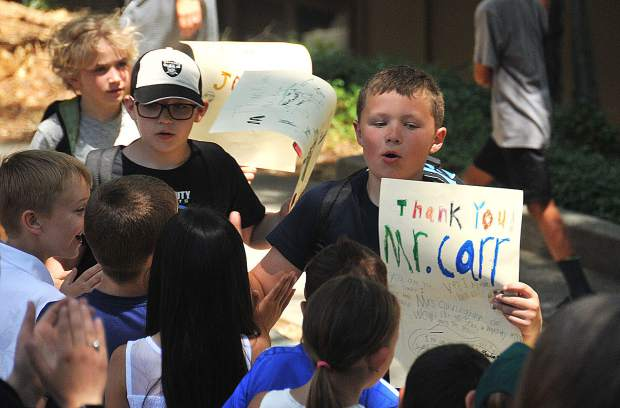 Outgoing Deer Creek Elementary School fourth-graders hold up signs during their