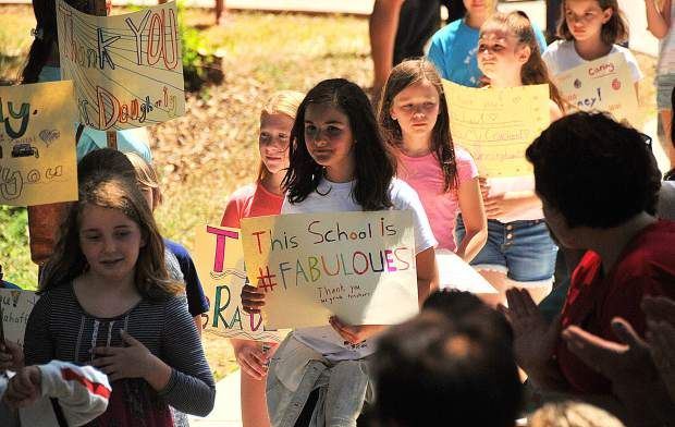 Outgoing Deer Creek Elementary School fourth-graders hold signs they've made to show appreciation to their teachers during the last day of school, Friday, where students were