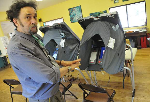 North San Juan poll worker Anthony Stewart, shows off Nevada County's electronic polling stations set up at the North San Juan Community Center's voting station.