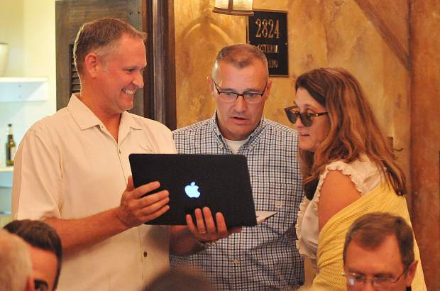 Nevada County candidate for Sheriff Bill Smethers (center) is shown the first set of election results released from the Nevada County elections office, which put him just behind Shannan Moon.