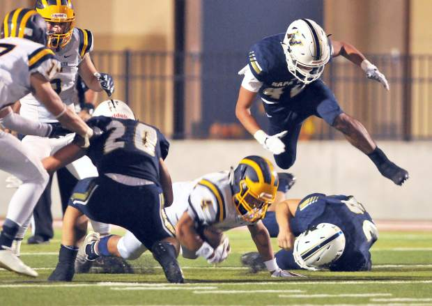 Nevada Union's Isreal Gonzales is hurdled by a Napa defender during a play Friday night at Napa High School.